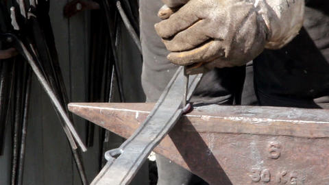 Blacksmith working on putting a hole in the steel  Footage