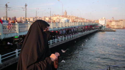 Woman dressed with black headscarf, chador eating, Stock Video Footage