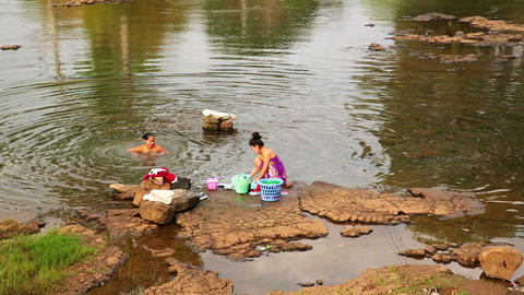 TAD LO, LAOS - MARCH 2014: Women washing clothes a Stock Video Footage