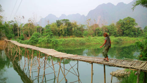 Tourist girl walking on bamboo bridge, vang vieng, Stock Video Footage