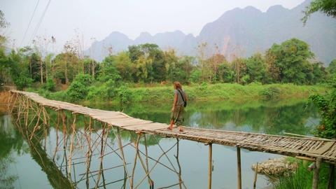 Tourist girl walking on bamboo bridge, vang vieng, Footage