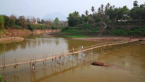 People crossing river on bamboo bridge, luang prab Footage