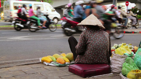Vendor woman sitting and selling fruits on heavy h Footage