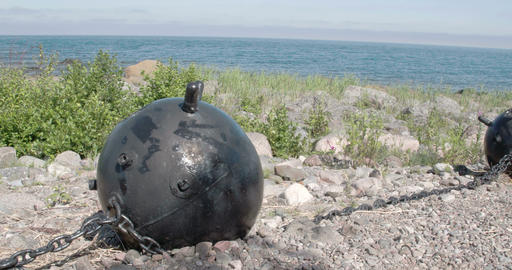 A big black sea mine on top of a hill near the sea Stock Video Footage