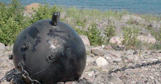 A big black sea mine on top of a hill near the sea Footage