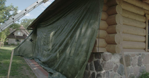 Workers covering the newly constructed cabin with  Footage