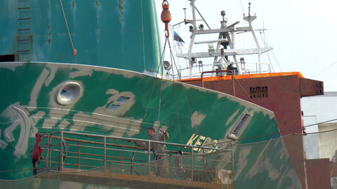 A ship worker repainting some green parts of the b Footage