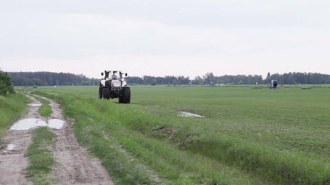 gray tractor rides on the green field Stock Video Footage