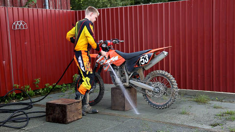 Motocross rider cleaning his dirt bike Stock Video Footage