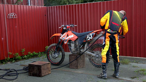 Motocross rider cleaning his dirt bike Footage