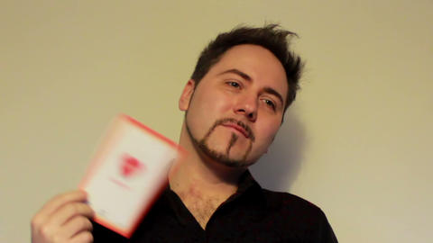Guy fanning a face with a Valentine's Day card Footage