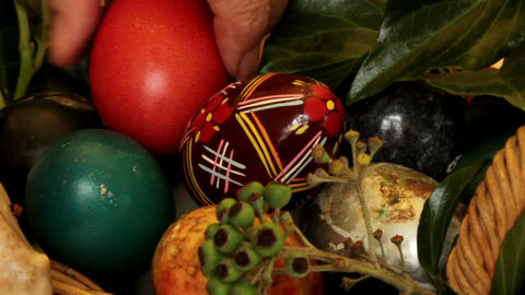 Older woman arranges Easter eggs in a basket - clo Stock Video Footage
