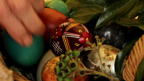 Older woman arranges Easter eggs in a basket - clo Footage