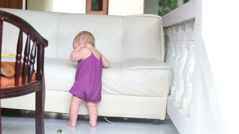 child eating cucumber standing leaning on the sofa Footage