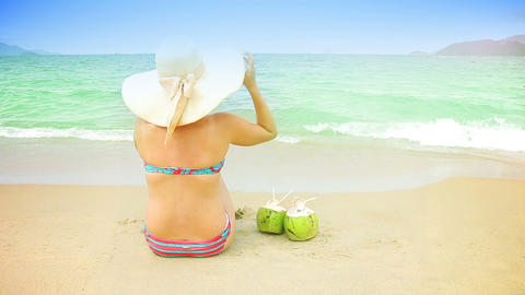 Young woman in swimsuit with coconut cocktail on t Stock Video Footage