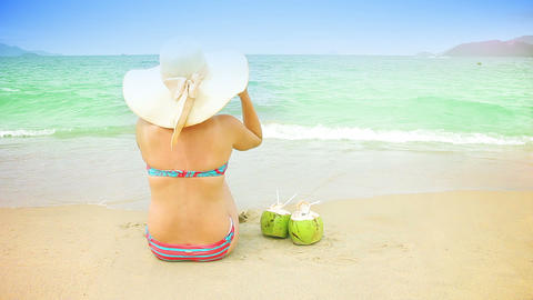 Young woman in swimsuit with coconut cocktail on t Live Action