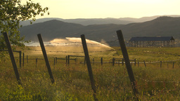 HD2009-7-2-6 irrigation in farm field evening, barb wire Stock Video Footage