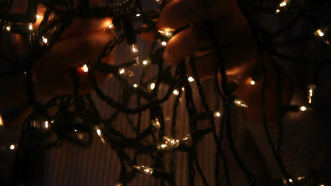 man untangling white Christmas lights Footage