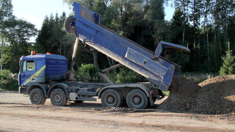 A dump truck unloading sand and soil; house Footage