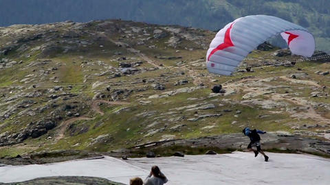 Man Paragliding Parachute On Snowy Mountain Area stock footage