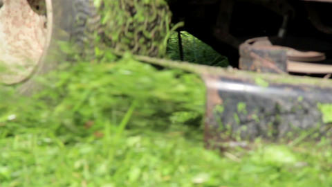 Red Lawn Mower Has Big Tires Running Over The Lawn stock footage