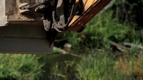 Backhoe carrying some soil and then dropping it of Footage