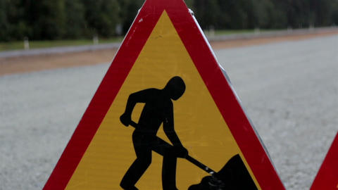 Men working road sign at the side of the road Footage