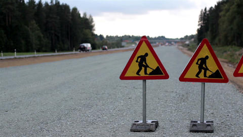Men working sign in the highway and cars passing o Footage
