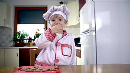 Child In Cook Outfit Trying Out Cookie stock footage