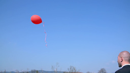 Red Balloon Flying In To Blue Sky In Slow Motion stock footage