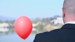 Man Looking At Red Balloon Flying Over Lake stock footage