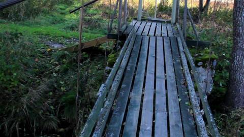 Walking On Wooden Bridge While Water Flowing Under stock footage