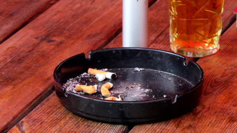 Ashtray with cigarette butts and a pint of beer Live Action