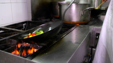 Chef frying vegetables in a wok and adding ladle of water Footage