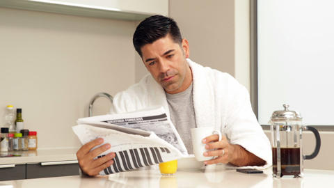 Handsome man drinking coffee and reading newspaper Footage