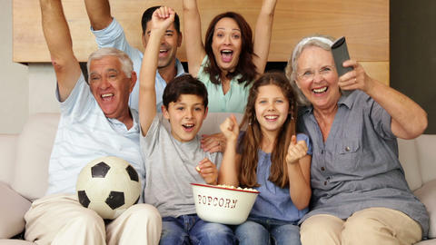 Happy extended family watching football on tv Footage
