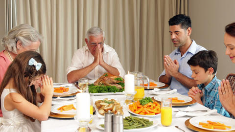 Extended family praying before dinner Live Action