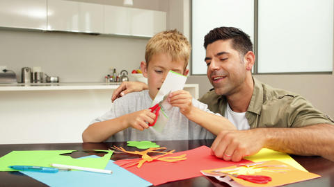 Happy father and son doing arts and crafts at kitc Footage