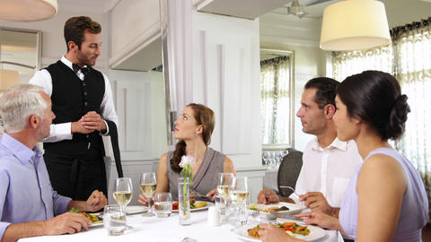 Waiter attending to a table of smiling friends Footage