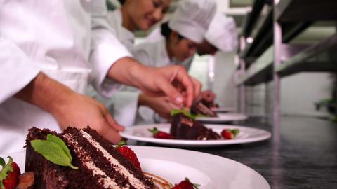 Team of chefs garnishing dessert plates with mint  Footage