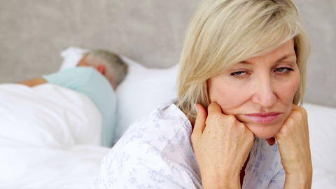 Unhappy woman thinking while her husband is sleepi Footage