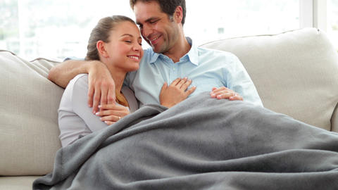 Cute couple lying on couch chatting under a blanke Footage