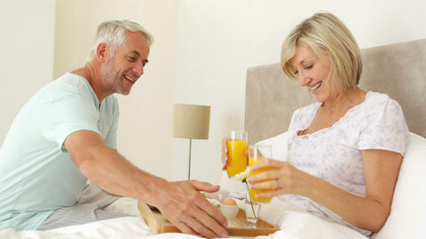 Romantic husband bringing his smiling wife breakfast in bed Footage