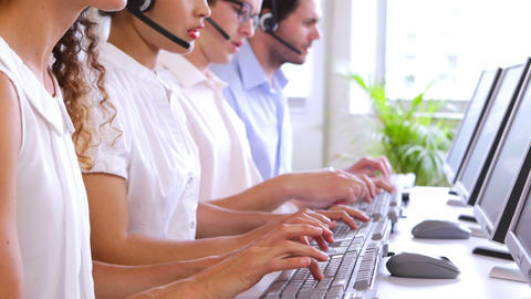 Row of call centre agents typing at their desk Footage