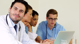Doctor smiling at camera while colleagues are talking Footage