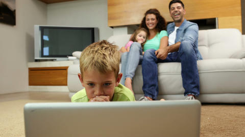 Little boy lying on floor using laptop with family Footage
