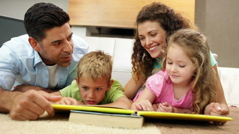 Siblings lying on floor reading book with parents Footage