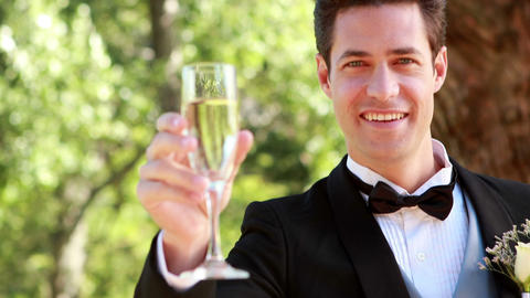 Happy groom smiling at camera and toasting with ch Footage
