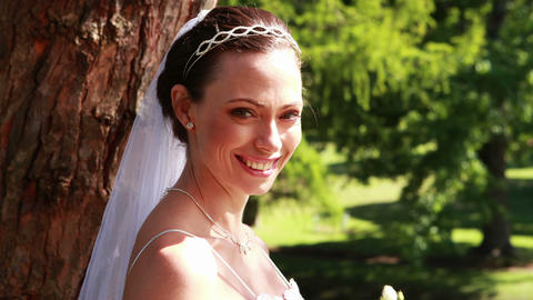 Pretty bride holding a bouquet in the park smiling Footage