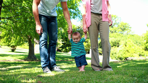 Parents teaching their baby son to walk on the gra Footage